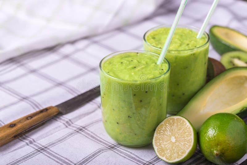 Groene die smoothie door avocado, citroen en kiwi op tafelkleedachtergrond wordt gemaakt stock foto's