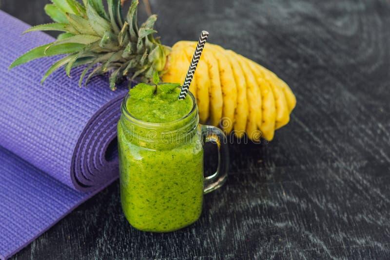 Groene die smoothies van spinazie en ananas en een yogamat wordt gemaakt Het gezond eten en sportenconcept stock afbeelding