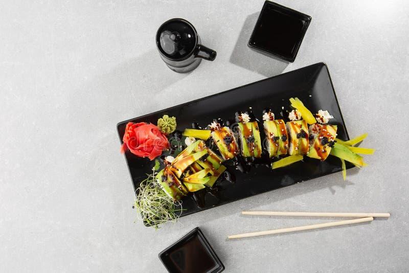 Groene draak sushi rol met paling, komkommer, zwarte sesamzaad en tobiko caviar, Japans voedsel Traditionele aziatische rijstsush royalty-vrije stock afbeeldingen
