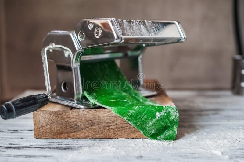 Groene eigengemaakte deegwaren van fettuccinespinazie van een noedelmachine stock afbeeldingen