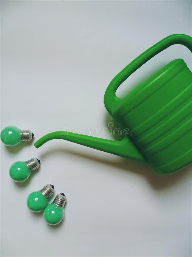 Groene elektrische bol en gieter voor het water geven van bloemen op een witte achtergrond stock afbeeldingen