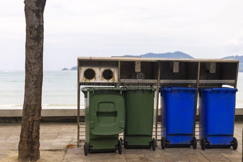 Groene en blauwe bak voor verschillende inzameling van Kringloopmaterialen op voetpad dichtbij strand royalty-vrije stock fotografie