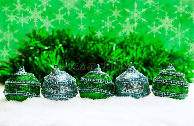 Groene en blauwe en zilveren Kerstmisballen in sneeuw met klatergoud en sneeuwvlokken, Kerstmisachtergrond stock afbeeldingen