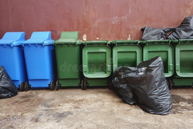 Groene en blauwe plastic kringloopbakken en zwarte vuilniszakken op r royalty-vrije stock afbeelding