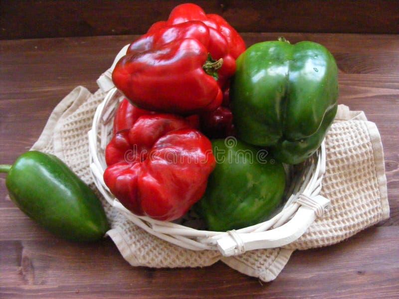 Groene en rode rijpe groene paprika op bruine achtergrond royalty-vrije stock fotografie