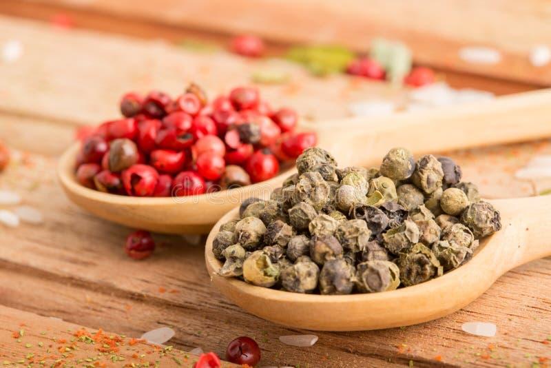 Groene en Spaanse peper in Houten Lepels stock afbeeldingen