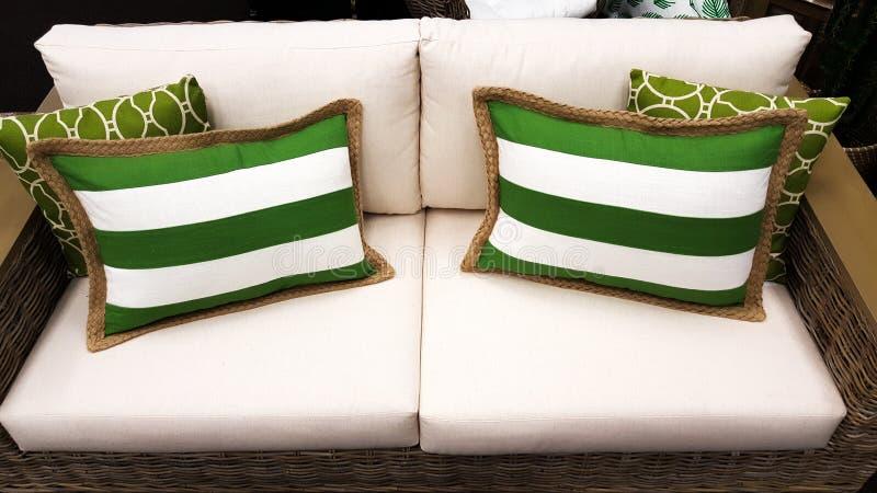 Groene en witte kussens op een bank zoals die door binnenlandse designe wordt gestileerd stock afbeeldingen