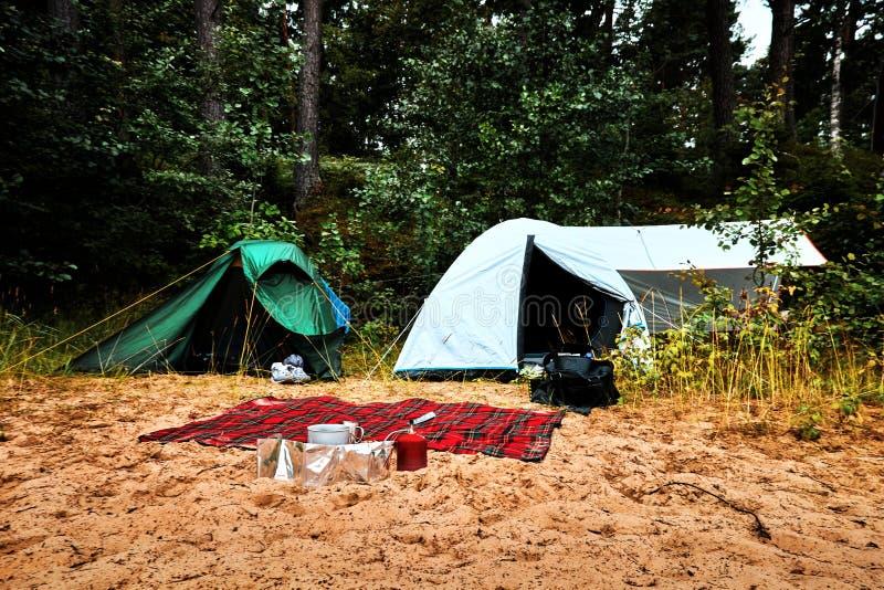 Groene en witte tent die zich bij een strand bij meer Vänern in Zweden met een wol deken en gasfornuis en het koken toestel bevi stock foto