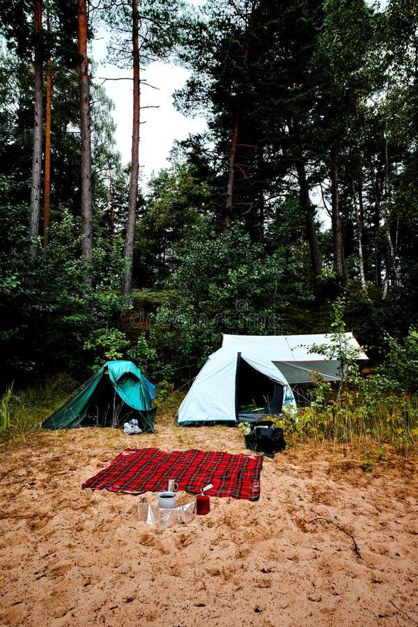 Groene en witte tent die zich bij een strand bij meer Vänern in Zweden met een wol deken en gasfornuis en het koken toestel bevi royalty-vrije stock fotografie