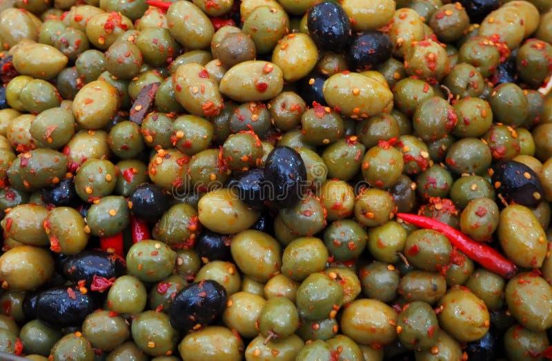 Groene en zwarte die olijven met hete Spaanse peperpeper worden gekruid Voedsel van de zuiden het Italiaanse specialiteit stock foto