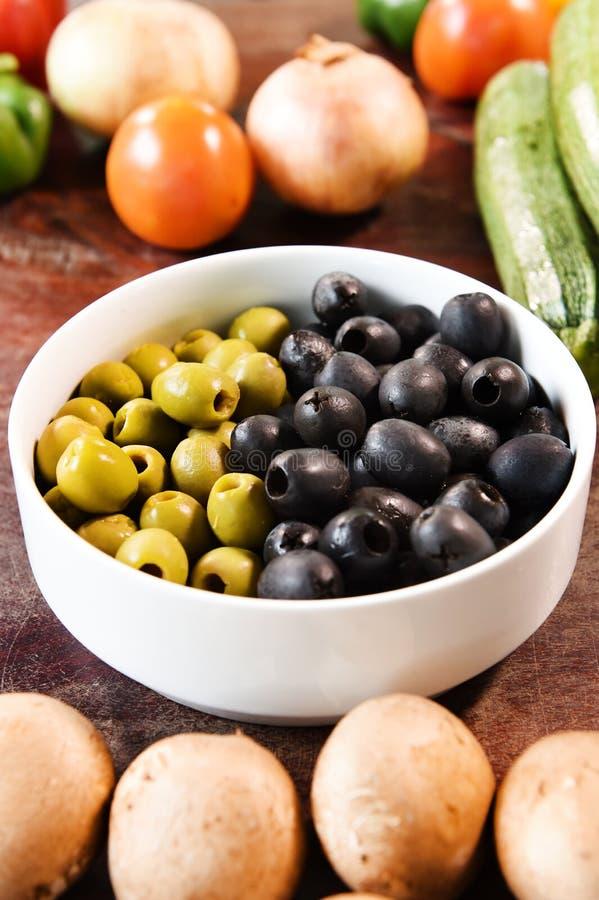 Groene en zwarte olijven in witte kom en ingrediënten voor pizza royalty-vrije stock fotografie