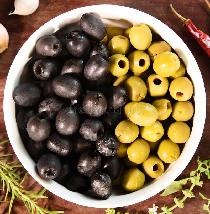 Groene en zwarte olijven in witte kom en ingrediënten voor pizza stock afbeeldingen