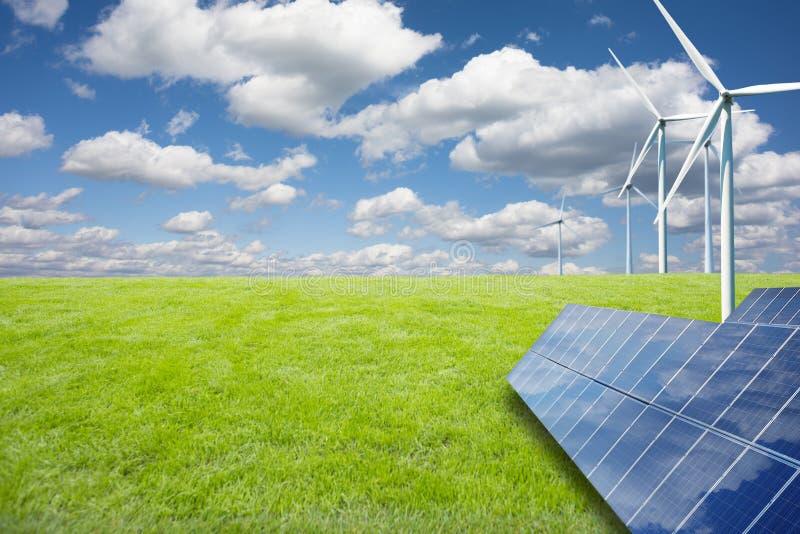 Groene energie van het de de aardconcept, zonnepanelen en windmolens op groene weide in een de zomerdag stock foto