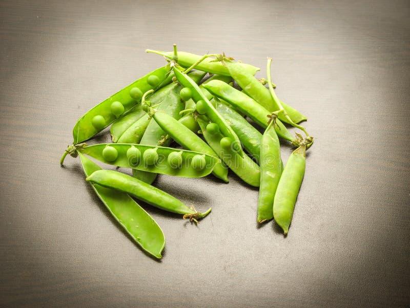 Groene erwten in de peulen op een houten lijst Rijpe peulen van groene erwten stock fotografie