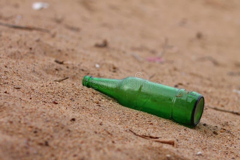 Groene fles op strandzand - de drank van de Partijviering - Verlaten fles stock afbeeldingen