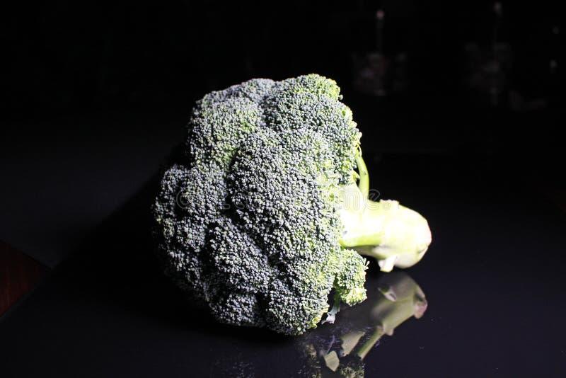 Groene gehele broccoli op zwarte weerspiegelende studioachtergrond Geïsoleerde zwarte glanzende spiegel weerspiegelde achtergrond royalty-vrije stock fotografie