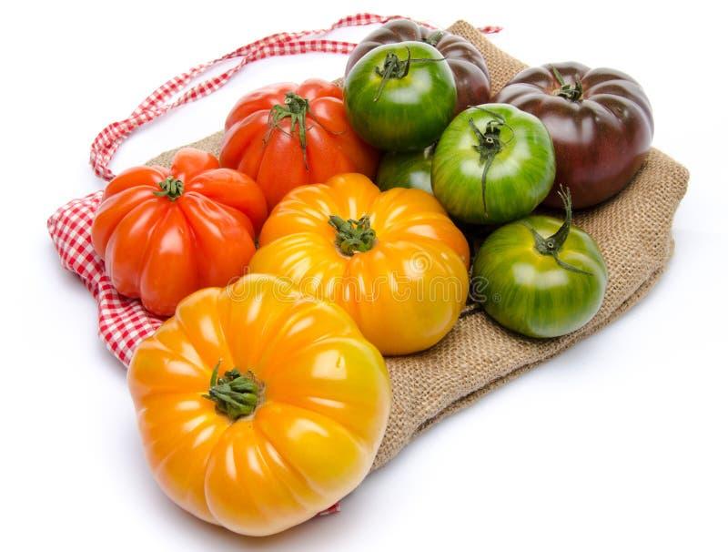 Groene, gele, oranje en purpere tomaten op een jute royalty-vrije stock afbeelding