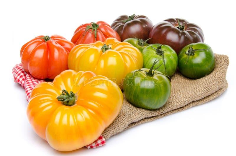 Groene, gele, oranje en purpere tomaten op een jute stock fotografie