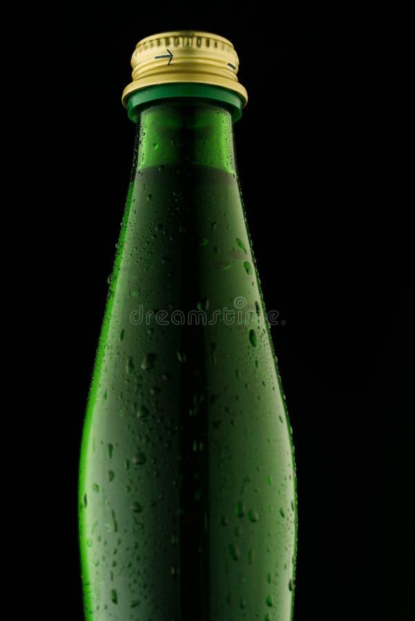 Groene glasfles op een zwarte achtergrond tegen het licht stock fotografie