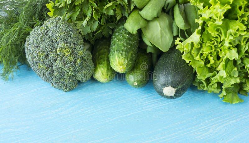 Groene groenten op een blauwe houten achtergrond Peterselie, spinazie, komkommer, broccoli, dille en courgette Hoogste mening Gro stock fotografie