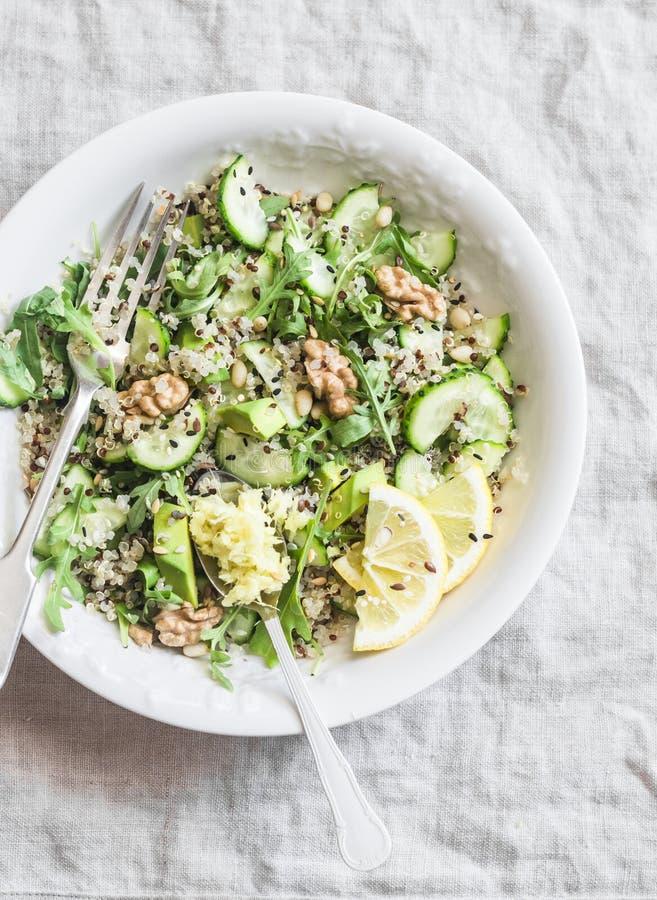 Groene groentenquinoa salade voor de lente detox Salade met quinoa, avocado, komkommers, arugula, okkernoten, gember en zaden Op  stock foto