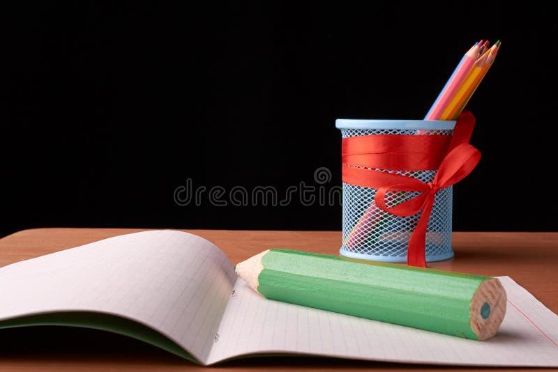 Groene grote pen en metaalkop met kleurpotloden op bureau op zwarte achtergrond stock afbeeldingen