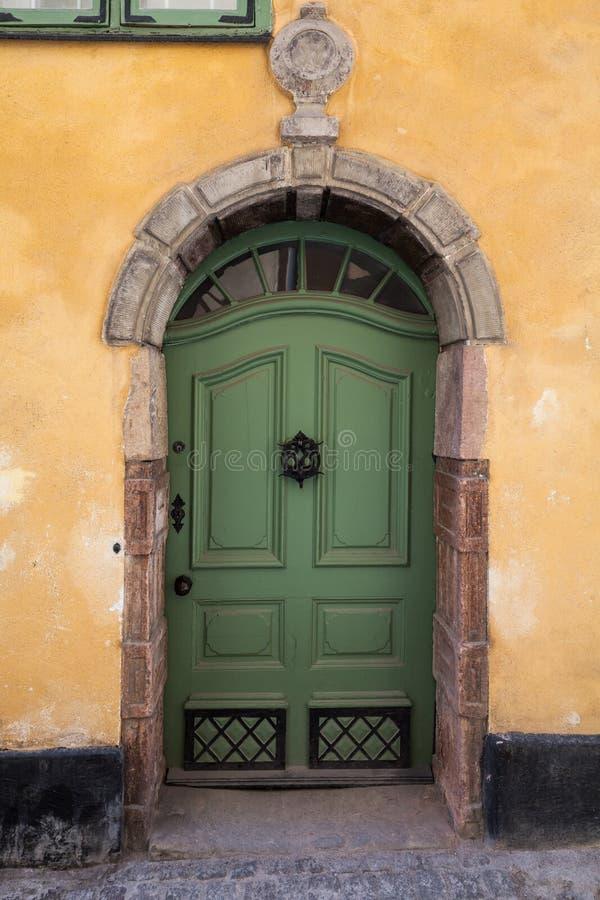 Groene houten deur in oude gele muur stock fotografie