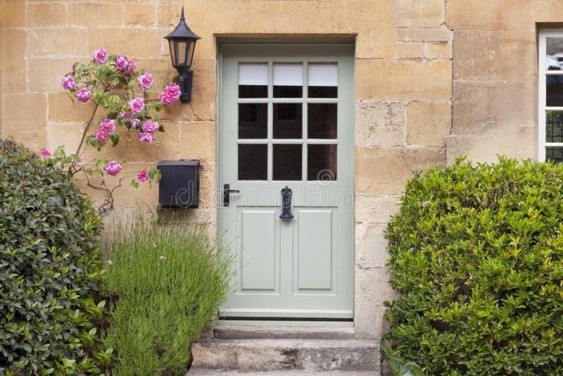 Groene houten deuren in traditioneel Engels plattelandshuisje in landelijk dorp stock fotografie