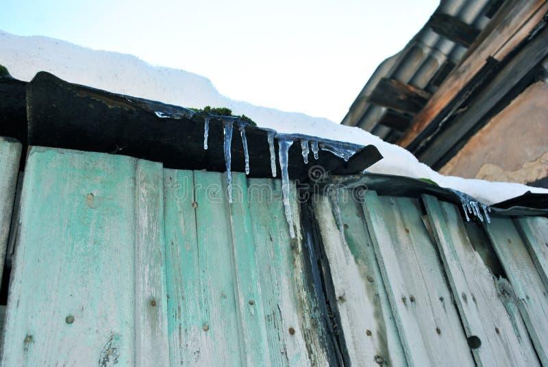 Groene houten oude muur met donker sjofel dak met ijskegels en witte sneeuw op bovenkant, mening van grond op blauwe duidelijke h royalty-vrije stock afbeeldingen