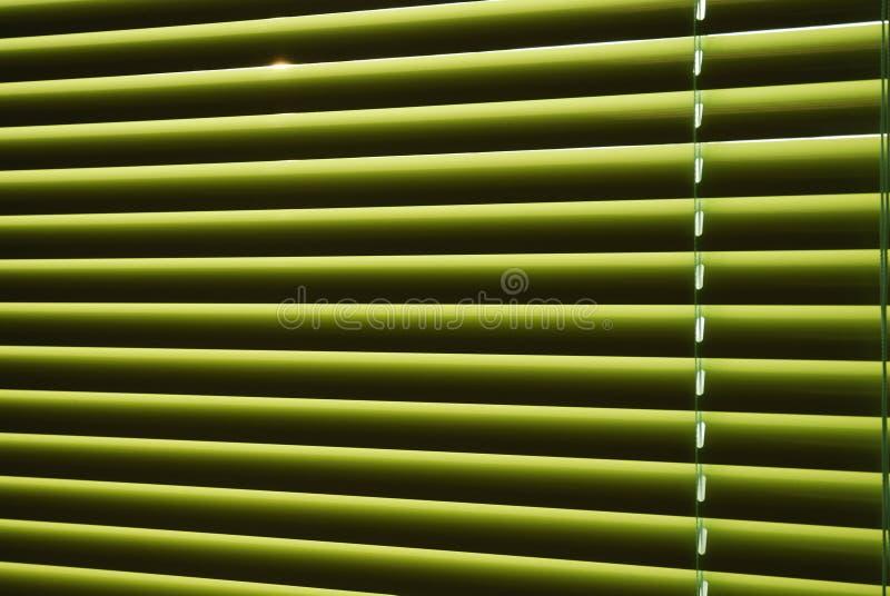 Groene jaloezie met strepen van licht stock foto