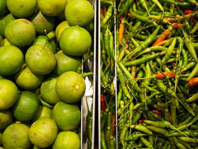Groene kalk en Spaanse pepers in het dienblad bij de markt stock foto's