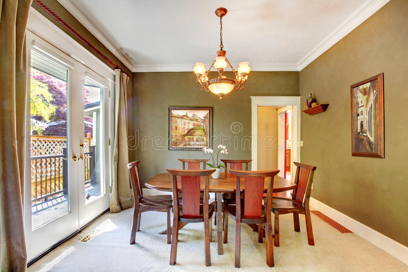 Groene klassieke eetkamer met kunst en grote deur. stock foto's