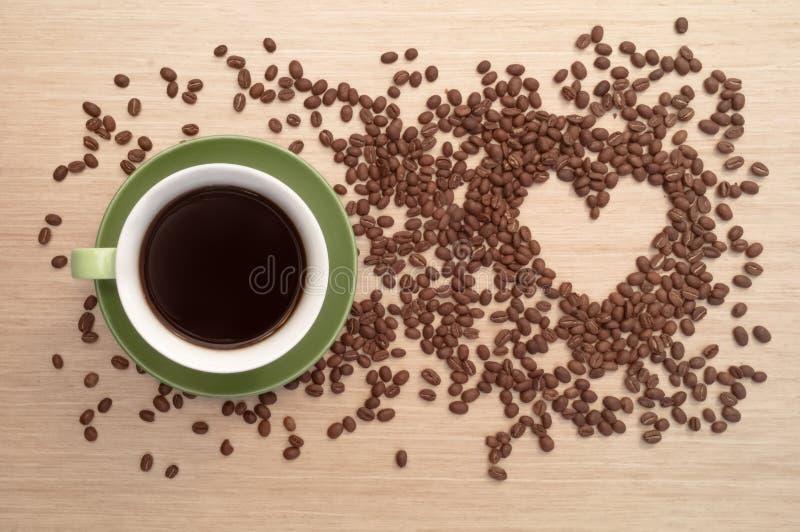 Groene koffiekop op het lijst en koffiehart royalty-vrije stock fotografie