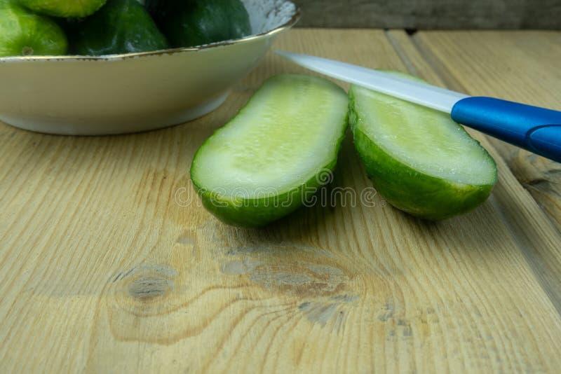 Groene komkommers op een plaat op de lijst Nabijgelegen die leugens een komkommer in half en een mes wordt gesneden Twee komkomme royalty-vrije stock foto's