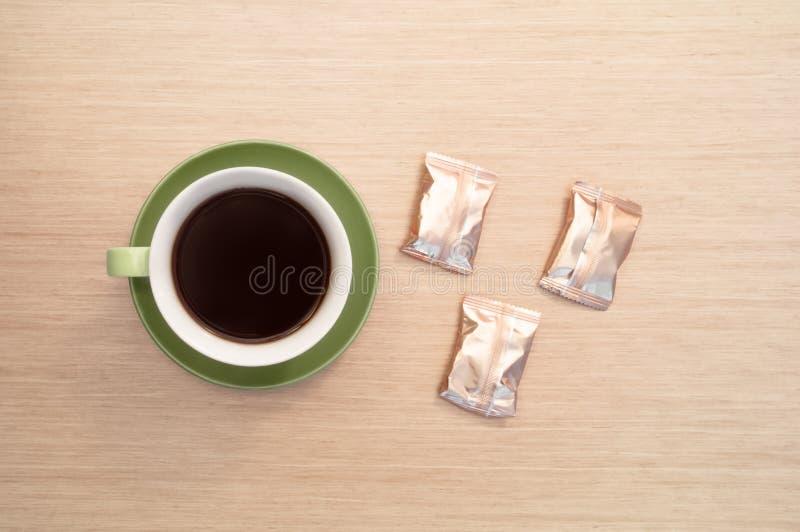 Groene kop van koffie op de achtergrond van de lijst en de snoepjes Mening vanaf bovenkant stock afbeelding