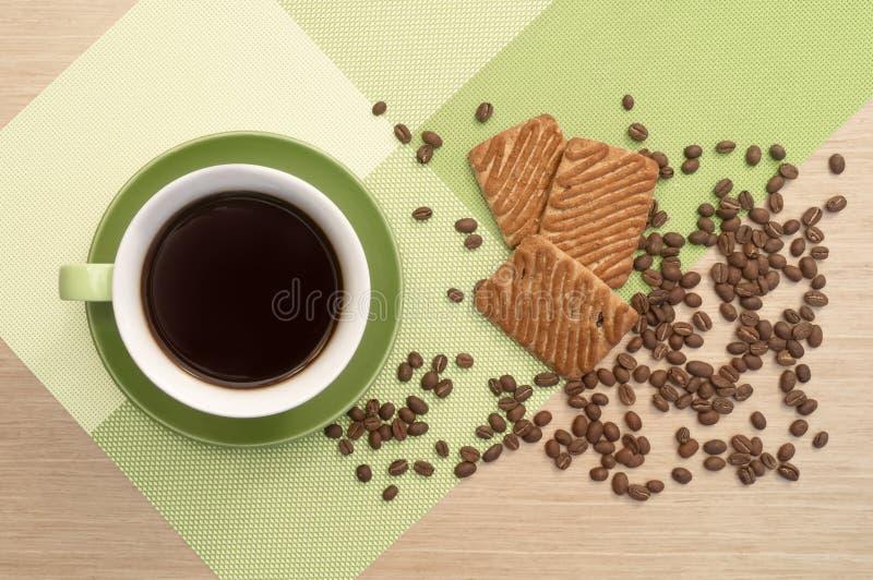 Groene kop van koffie op de lijst en het koekje en bonen Mening vanaf bovenkant stock foto's