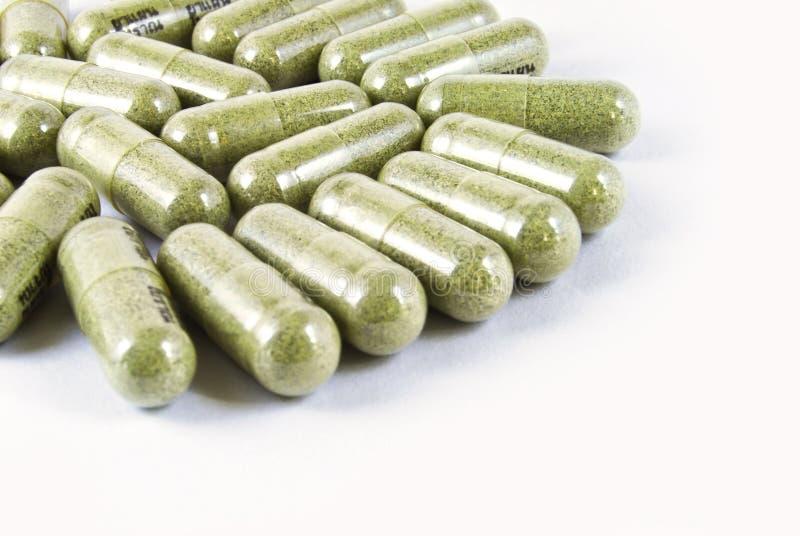 Groene kruiden geïsoleerdes geneeskundecapsule stock foto