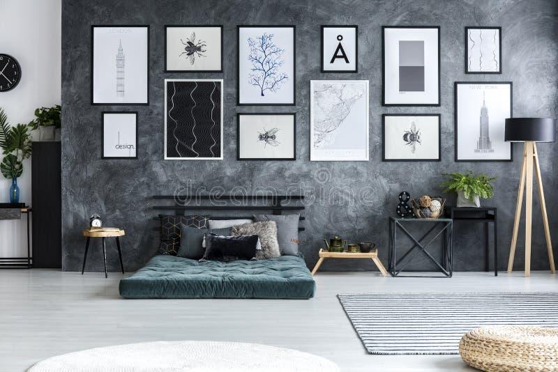 Groene matras tegen concrete muur met binnen galerij van affiches stock foto