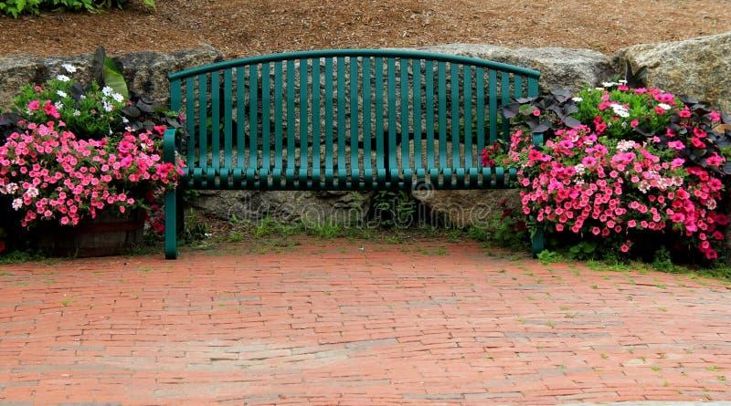 Groene metaalbank op schitterend baksteenterras royalty-vrije stock afbeelding