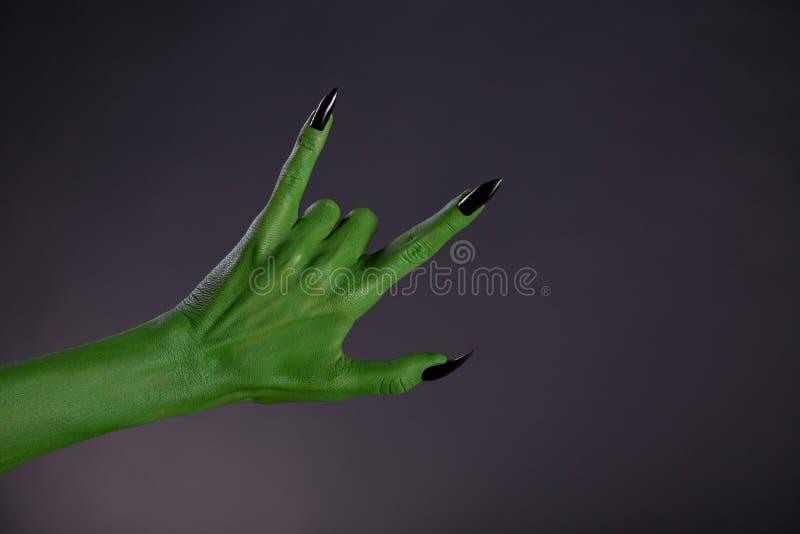 Groene monsterhand die zwaar metaalgebaar tonen royalty-vrije stock afbeeldingen