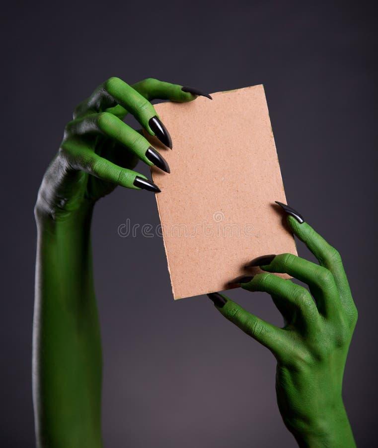 Groene monsterhanden die leeg stuk van karton houden stock foto