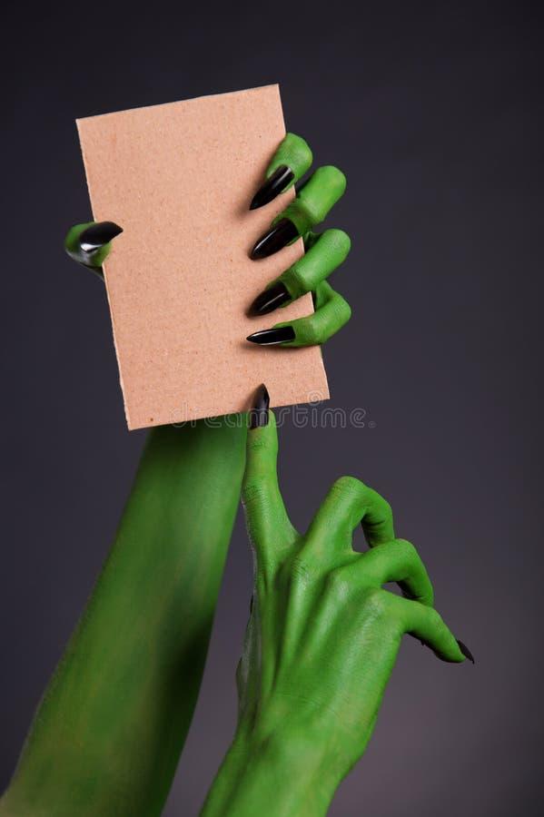 Groene monsterhanden met zwarte spijkers die leeg stuk van kaart houden stock foto