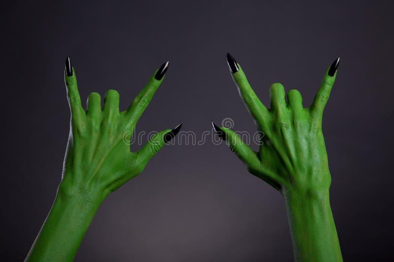Groene monsterhanden met zwarte spijkers die zwaar metaalgebaar tonen stock foto's