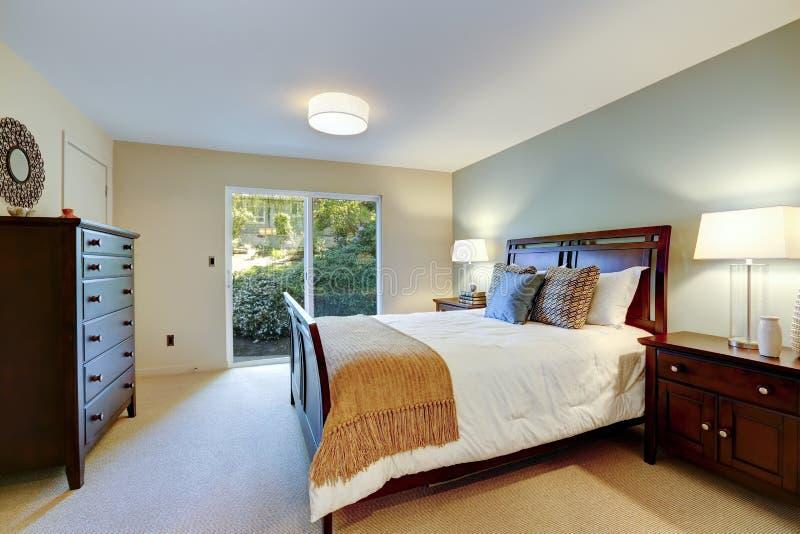 Groene mooie slaapkamer met klassiek meubilair en deur aan tuin. stock fotografie