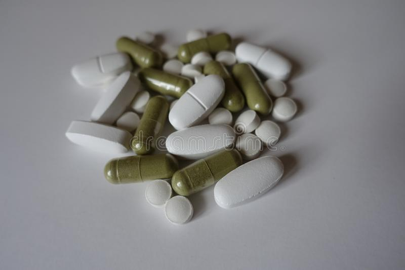 Groene moringa capsules, witte calciumdragees en vitaminek tabletten stock afbeeldingen