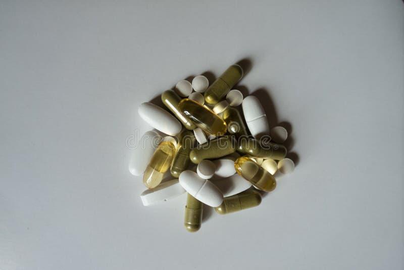 Groene moringa en gele vistraancapsules, witte calciumdragees en vitaminek2 tabletten stock afbeelding