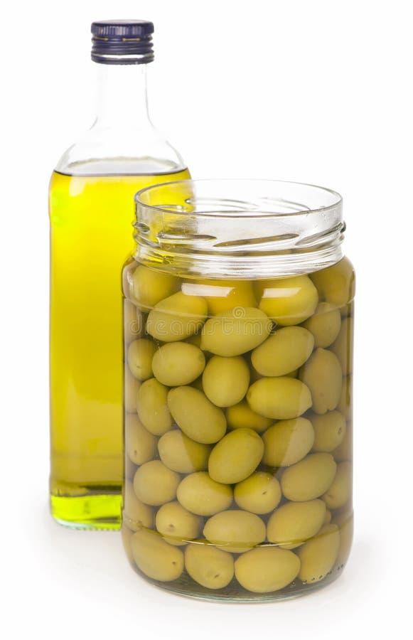 Groene olijven die in bank en een fles worden bewaard van stock foto's