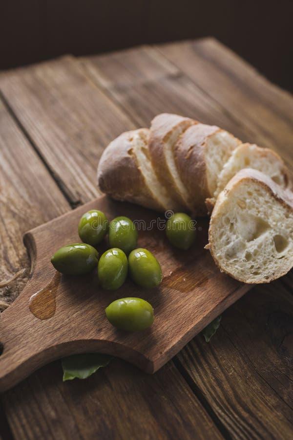 Groene olijven, gesneden ciabatta, stock foto's