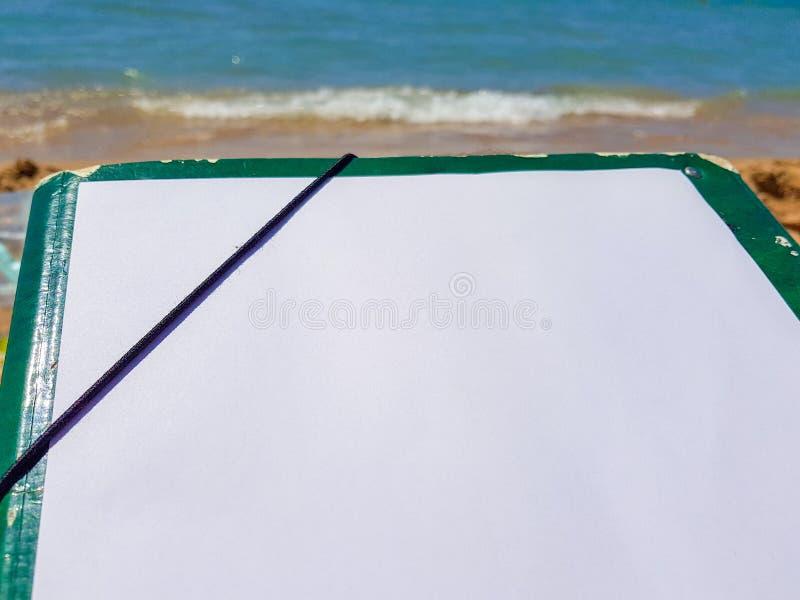 Groene omslag met een wit blad op het strand Beeld om studies en vakantie te begeleiden stock fotografie