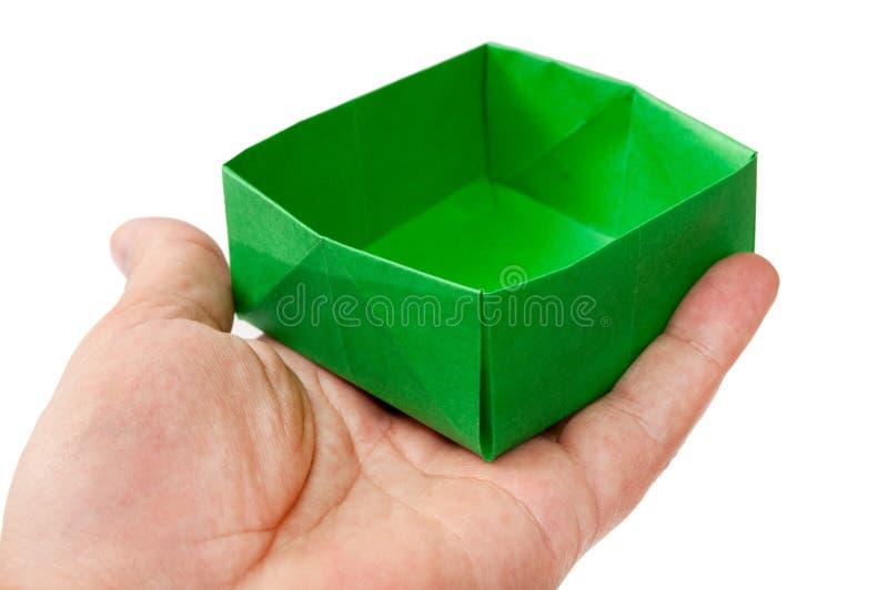 Groene origamidoos in de hand stock afbeelding